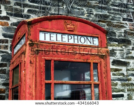 Detail of old telephone box; Traditional UK red telephone box; paintwork  faded and peeling due to weathering and age