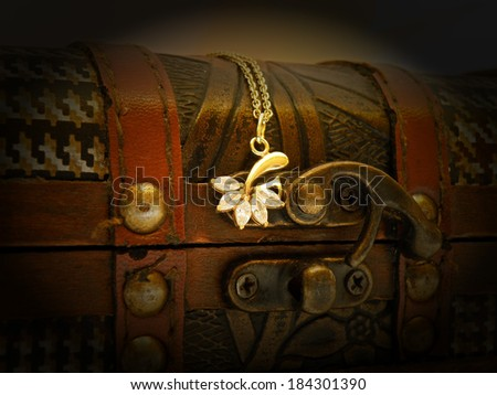 Detail of old treasure chest with gold chain. Dark background. - stock photo