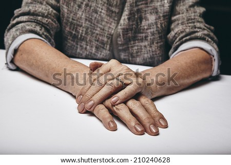 Detail of old woman's hands resting on grey surface. Senior female's hand on top of another while sitting at a table. - stock photo