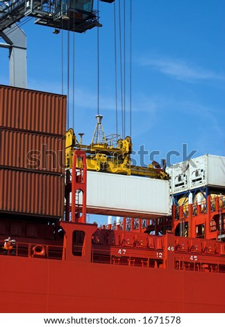 Detail of one container being loaded into a cargo ship (all brand names and logos have been removed) - stock photo