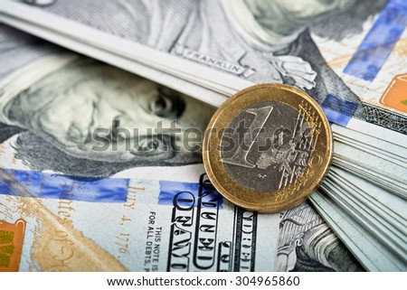 Detail of one euro coin, over dollar notes in background - stock photo