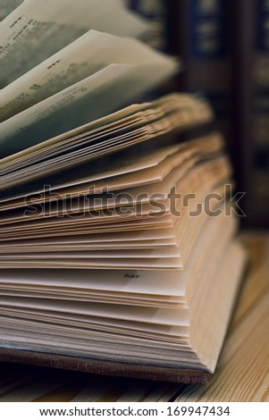 Detail of open book in dark colors - stock photo
