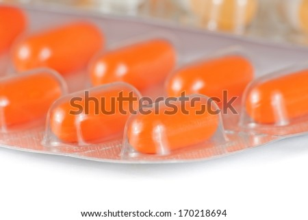 detail of orange pills packed in blister isolated on white table - stock photo