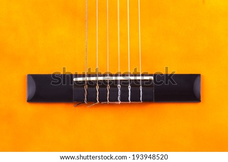 Detail of orange wooden classical acoustic guitar. - stock photo
