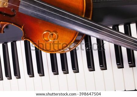 Detail of piano keyboard, old violin and wedding rings - stock photo