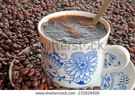 Detail of porcelain cup of coffee with spoon and saucer in pile of brown coffee beans - stock photo