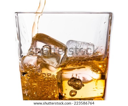 detail of pouring scotch whiskey in glass with ice cubes isolated on white background - stock photo