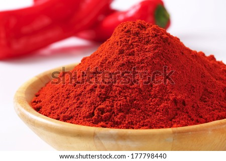 detail of red pepper powder in the wooden bowl - stock photo