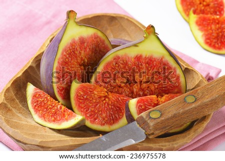 detail of ripe sweet fig, served in the wooden bowl with sharp knife - stock photo