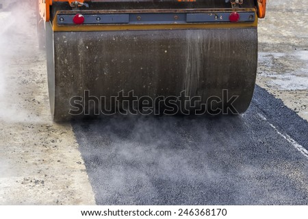 Detail of road roller during asphalt patching works. Selective focus. - stock photo