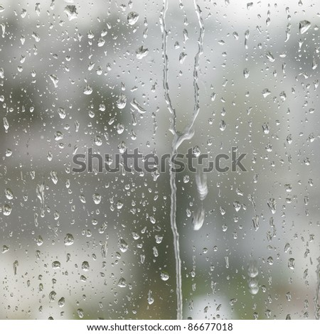 detail of roll off raindrops on window glass - stock photo