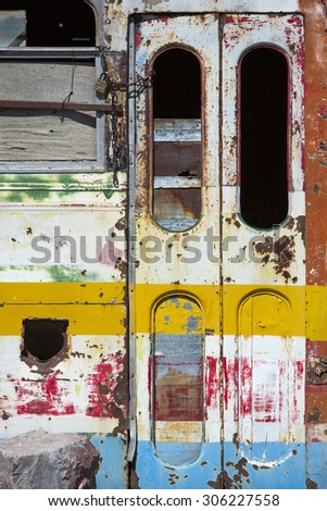 Detail of rusted old colored bus with broken windows abandoned in the countryside in the North of Argentina near San Juan. - stock photo