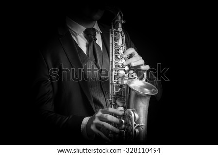 Detail of Saxophone and man hands isolated against black background. Close up studio portrait, black and white image. - stock photo
