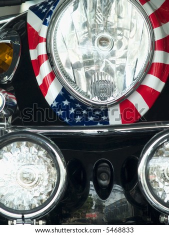 Detail of scooter with the pattern of the American flag wrapped around the headlight. - stock photo