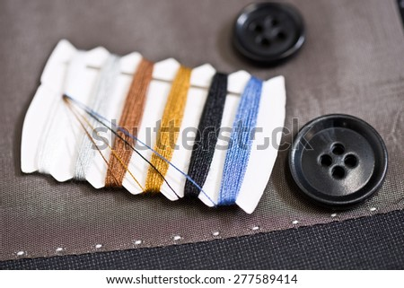 detail of sewing kit on the gray clothing - stock photo