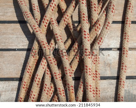 detail of ships rope with teak deck behind - stock photo