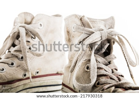 Detail of shoelaces on grunge white sneakers on white background. Isolated objects. - stock photo