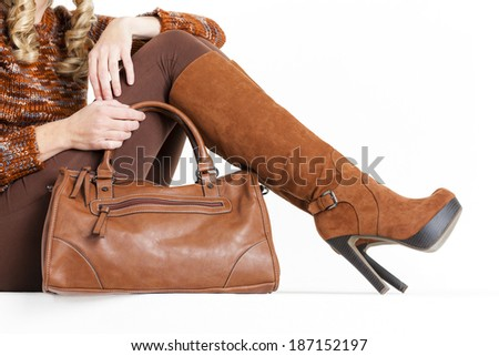 detail of sitting woman wearing brown clothes and boots with a handbag