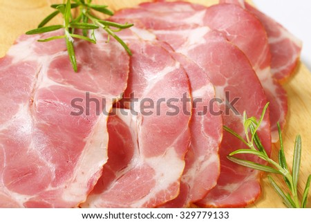 detail of smoked pork neck slices on wooden cutting board