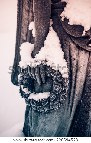 Detail of snow covered hand holding the wreath of the woman sculpture in the cemetery of small town church. Atmospheric photo. Black and white photography. Sepia. Cream tone. - stock photo