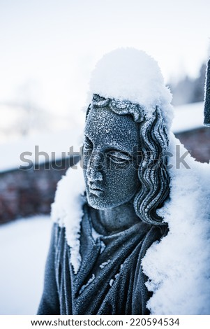Detail of snow covered woman face of sculpture in the cemetery of small town church.  - stock photo