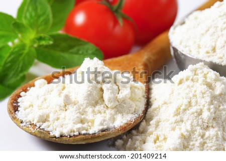 detail of soft wheat flour on the wooden spoon, with fresh tomatoes in background