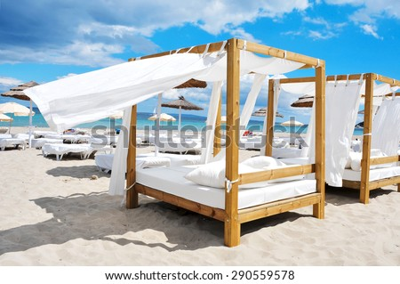 detail of some beds and sunloungers in a beach club in a white sand beach in Ibiza, Spain - stock photo