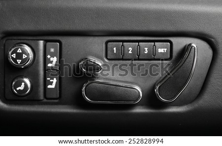 Detail of some buttons for adjusting the chair position, in a car.
