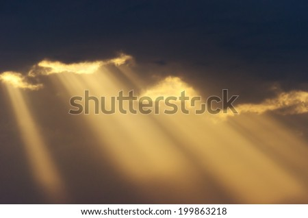 Detail of some fluffy clouds and rays of sunlight shining through the opening sky. - stock photo