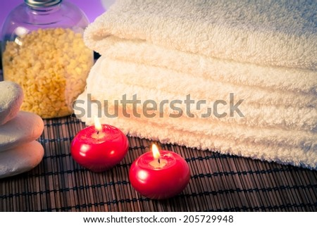 detail of spa massage border with towel stacked stone and red candles on wood background warm atmosphere - stock photo