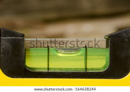 Detail of spirit level with glass cover and yellow base - stock photo