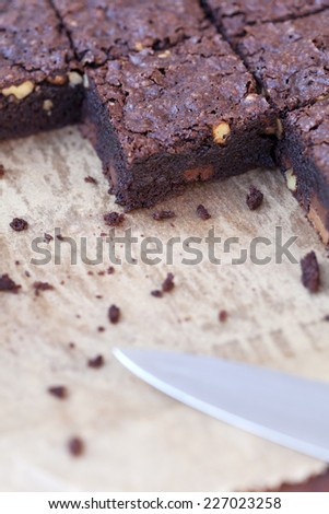 detail of square of brownies cut with knife on baking paper