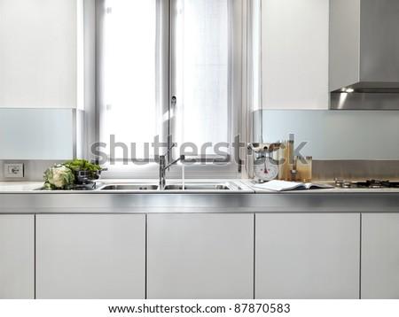 detail of steel sink under the window in a modern white kitchen - stock photo