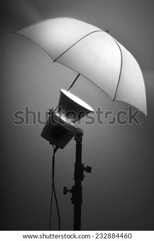 Detail of studio flash strobe light and umbrella on stand strobist professional photographer - stock photo
