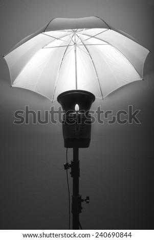 Detail of studio flash strobe light and umbrella on stand strobist professional photographer - stock photo