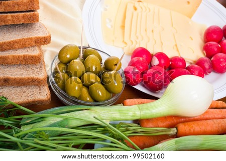 Detail of table with fresh vegetable, olives, cheese and bread.