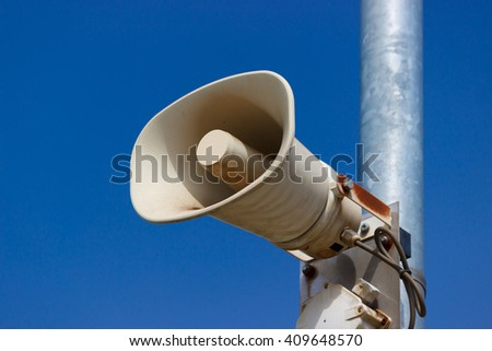 Detail of tannoy (loudspeaker) on the rod, blue sky, shallow depth of field.