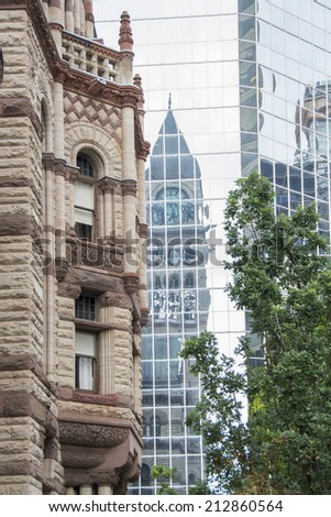 Detail of the architecture of the old city hall in Toronto and a reflection of its tower in a nearby highrise. - stock photo