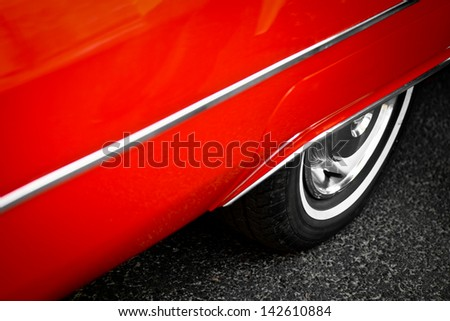 Detail of the back wheel of a vintage red car - stock photo