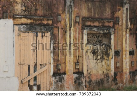 Detail of the entrance of an ancient colonial building in Grand Bassam Ivory Coast. The wall and the door were painted in brown and are now decrepite. Pattern with vertical lines and pillar.