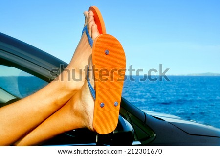 detail of the feet of a young man wearing flip-flops who is relaxing in a car near the ocean - stock photo