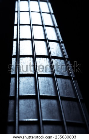 Detail of the fret board of a bass guitar, on a dark background.