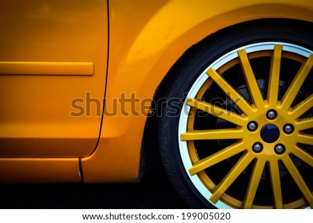 Detail of the front wheel of a yellow car. - stock photo
