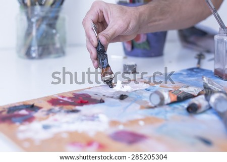 detail of the hand of a male painter adding paint to the palette at his painting studio - focus on paint - stock photo