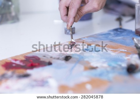 detail of the hand of a male painter mixing paint with the palette knife over the palette at his painting studio - focus on palette knife - stock photo
