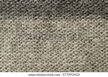 detail of the handmade knitted pattern (two different shades of gray) of wool and alpaca winter yarn - stock photo