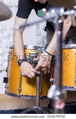 detail of the hands of a sound engineer adjusting a drum in a recording studio - focus on the center of the image - stock photo