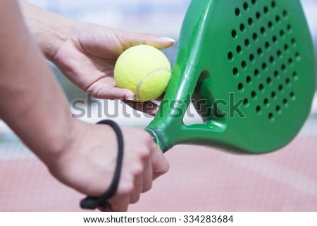 detail of the hands of a woman is ready for serve and holding ball and racket of paddle - focus on the ball