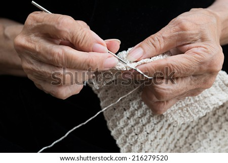 Detail of the hands of an elderly person crocheting
