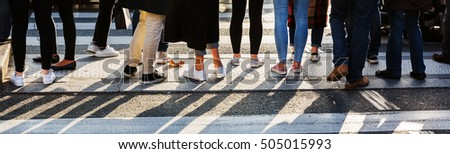 detail of the legs of a crowd of people waiting at the pedestrian crossing